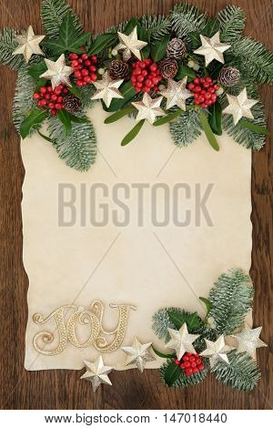 Christmas abstract background border with gold glitter joy sign and star decorations,  holly, ivy, mistletoe and snow covered fir on parchment paper over oak.