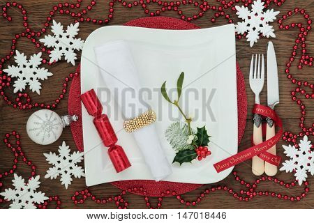 Christmas dinner table setting with white porcelain plate, cracker, holly, mistletoe, napkin, snowflake baubles, red bead decorations antique cutlery and ribbon over oak wood background.