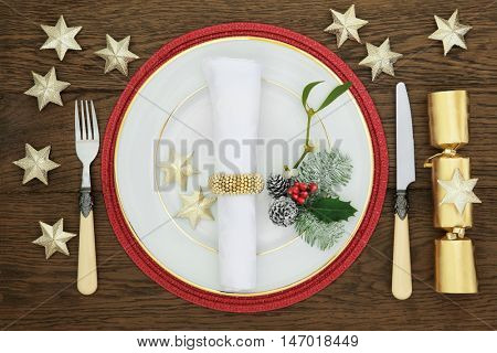 Christmas dinner decorative table setting with white porcelain plate, cutlery, linen napkin, holly, mistletoe, fir,  gold cracker and star decorations over oak background.