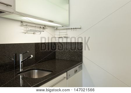 domestic kitchen of empty apartment, black counter top