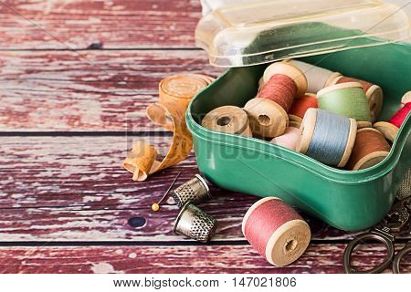 Box with a spools of thread, measuring tape, scissors and thimbles on an old wooden table.