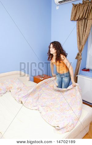 A teen girl happily making her bed in her room.