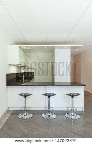 domestic kitchen of empty apartment, counter top with stools