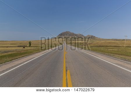 A highway leading to a mountain like butte.