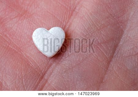 The tablet in the form of heart lay on the hand close up