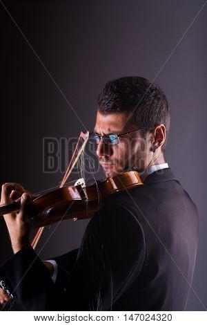 Violinist  playing a broken  violin on dark background,