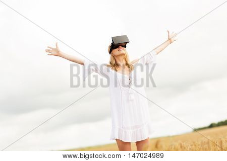 augmented reality, gaming, summer holidays, technology and people concept - happy young woman with virtual reality headset or 3d glasses on cereal field with raised hands