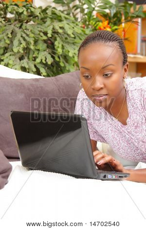 Beautiful young woman using laptop at home