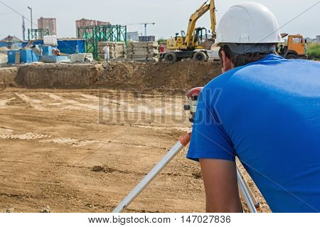 Surveyor engineers working with total station on road construction site