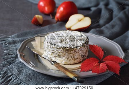 Bleu cendre french mould cow's milk cheese and red pears on dark background