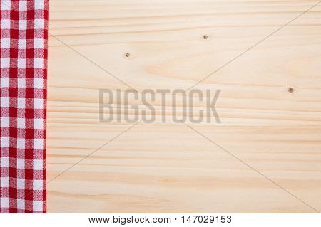 Checkered tablecloth red on the wooden background/ texture