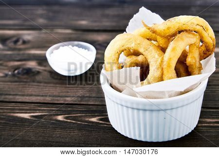 Tasty, crunchy, golden onion rings in a white bowl with a paper. Dark wood background, a cup of salt next to it. Appetizing delicious flavorful snack from the deep fryer.