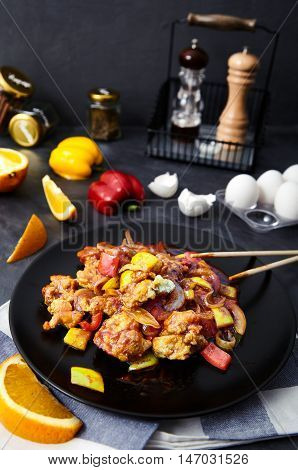 Stir fried chicken with onion, bell pepper, scrambled egg and soy sauce on a black plate with chopsticks. Asian meal on a black background, with a towel, a slice of orange and an egg shell