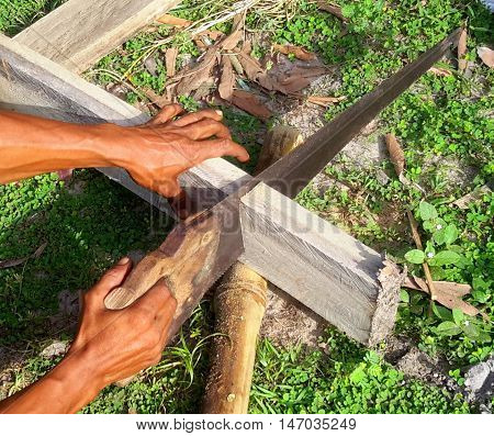 Thai man sawing a board with a hand saw outdoors, using a piece of bamboo to support the board, Songkhla, Thailand