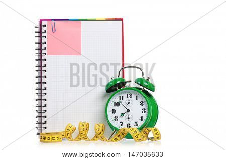 Concept of diet - alarm clock, measuring tape and blank notebook, isolated on white background. Time of starting a diet plan.