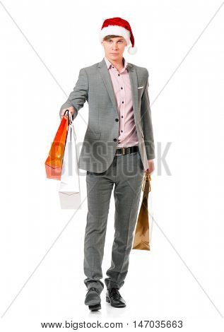Caucasian man wearing christmas hat for santa. Young businessman in gray suit with shopping bags isolated on white background. Successful boy wearing Santa Claus hat - full lenght portrait.
