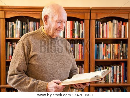 Man Standing And Reading Book In Library