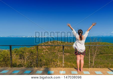 Happy young woman spreading hand for relaxing and enjoy with the sea view.
