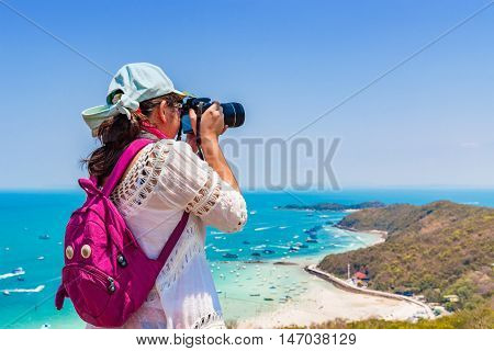 Young woman is taking a beach photo at the top of the island.
