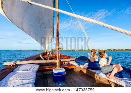Kids sailing in a traditional African dhow boat on sunset