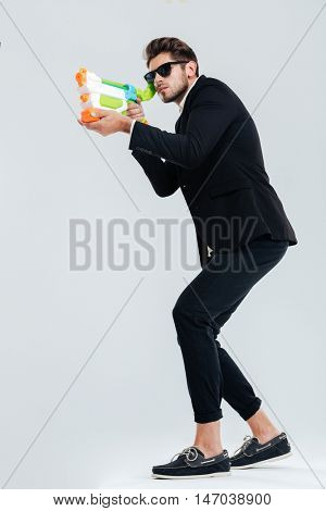 Full length portrait of focused businessman in sunglasses and suit shooting with water gun over gray background