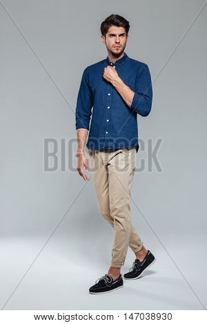 Full length portrait of a casual handsome young man fastening button isolated on a gray background