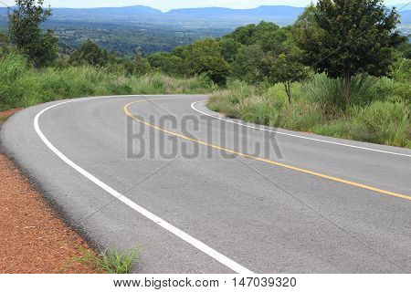 Black asphalt winding Road transport going to the distance with yellow line drawing separated two way of forward and backward