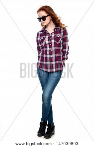 Beautiful girl in sunglasses in a full-length isolated on white background. Young pretty curly woman in plaid shirt and jeans posing