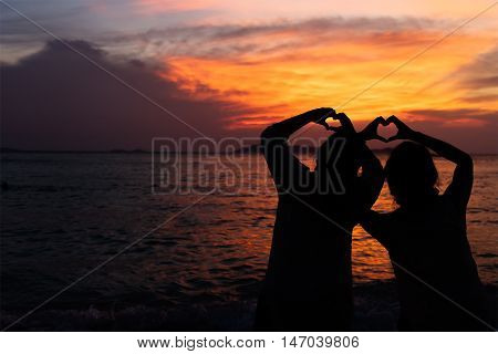 People makes heart symbol with hand at dusk.