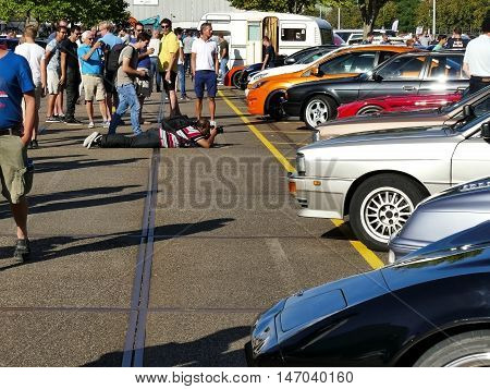 Amsterdam, The Netherlands - September 10, 2016: Man Lying On Ground Photographing Cars On Display D