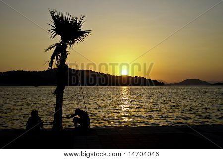 people fishing at sunset