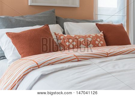 Orange Color Tone Pillows Set On Bed In Modern Bedroom