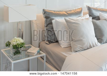 Pillows Set On Bed With Vase Of Flower In Luxury Bedroom