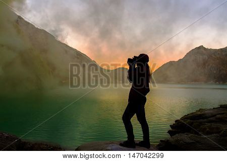 Silhouette of woman is taking photo at crater lake of vocalno before sunrise.