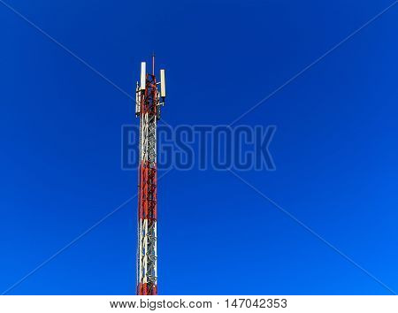 Red and white color telecommunication tower on clear blue sky