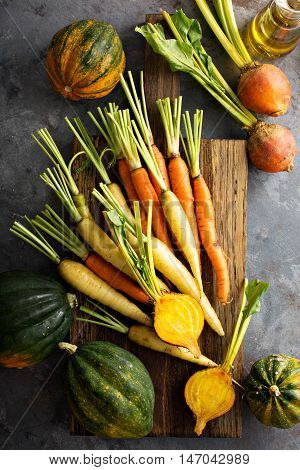 Big pile of autumn produce with carrots, yellow beets and squash ready to be cooked