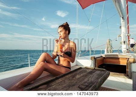 Young beautiful brunette girl drinking cocktail while resting on a yacht