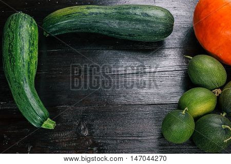 Orange pumpkin, zuccini and green melons on the dark wood table