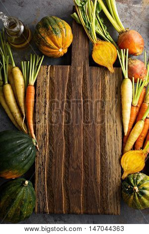 Autumn vegetables background, carrots, beets and squashes around a cutting board