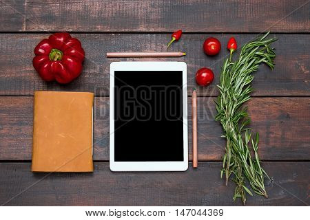 The tablet notebook fresh bitter and sweet pepper on wooden background