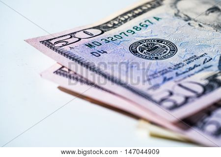 Fifty dollar bills laying on a white background - money finance imagery