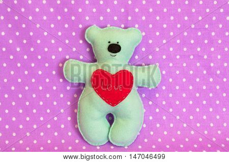 Blue felt bear on purple background, hand-stitched toy, a craft out of felt
