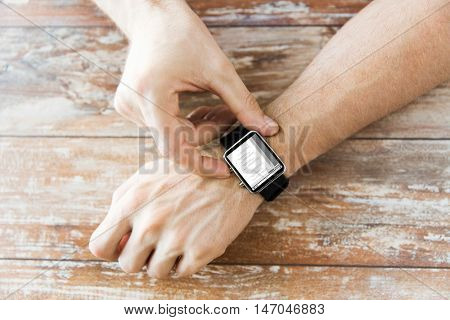 business, modern technology, programming and people concept - close up of male hands setting smart watch with coding on screen on wooden table