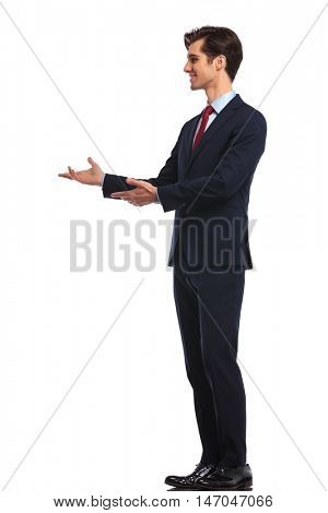 side of a young smiling business man presenting something with both hands on white studio background