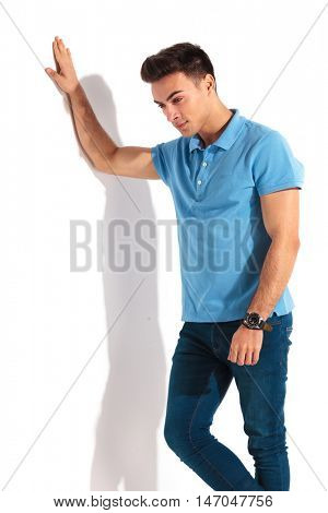 sad casual man in polo shirt is looking down while leaning hand on white wall
