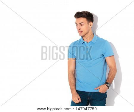 anxious man biting his lip and looks to a side , standing against white wall