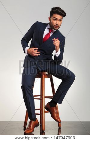 side view picture of a young business man in elegant modern suit sitting on a stool and looks away from the camera