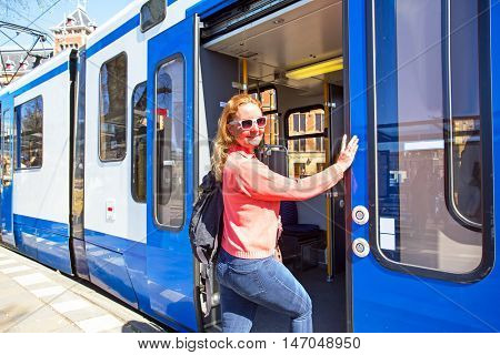 Young native dutch woman getting on the tram at the station in Amsterdam Netherlands