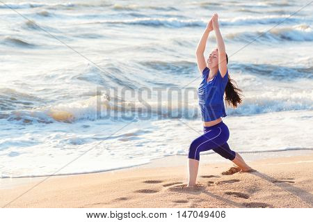 Woman practicing warrior yoga pose outdoors on sunrise on sea or ocean background. Female doing yoga warrior or virabhadrasana pose at the beach with copy space. Yoga. Warrior or virabhadrasana pose