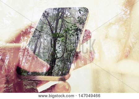 concept image of Digital composite using cell phone in forest